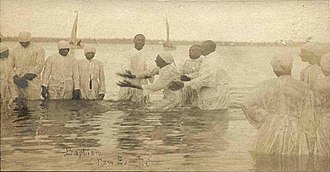 "Black church - ""Wade in the water."" A postcard of a river baptism in New Bern, North Carolina, around 1900."