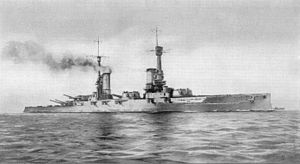 A large gray warship bristling with guns, with a tall mast and two smoke stacks, sits on a calm sea