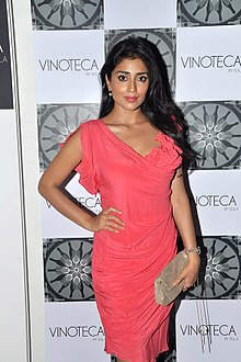 Shriya Saran, with her right hand on hip, posing for the camera.