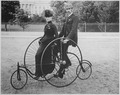 Smartly dressed couple seated on an 1886-model bicycle for two - NARA - 519711.tif