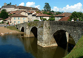 The Romanesque bridge in Solignac, with the abbey and surrounding buildings beyond