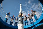 Soyuz MS-12 crew and backup crew at the Soyuz rocket monument behind the Cosmonaut Hotel.jpg