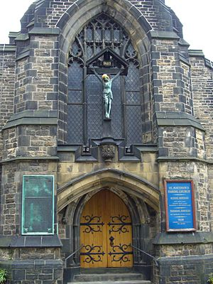 St Matthew's Church, Sheffield - The main entrance on Carver Street with the War Memorial plaque to the left and Crucifixtion statue above.