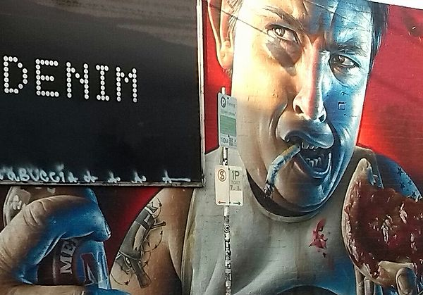 Melbourne street art of a stereotypical male bogan. He is depicted as a repulsive character with a cigarette in his mouth, a tomato sauce-covered meat pie in one hand and a stubby of Melbourne Bitter in the other. On his arm is a tattoo of bushranger and outlaw Ned Kelly.