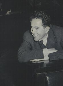 Man wearing a dark suit, smiling and leaning forward