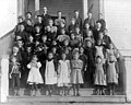 Students standing with teacher AS Burrows on the front steps of the two-room school house at Main St and 100th Ave SE, Bellevue (WASTATE 1816).jpeg
