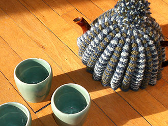 Tea cosy - A textured, hand knitted tea cosy on a teapot