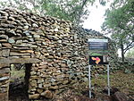 A picture of a stone wall with a gate.