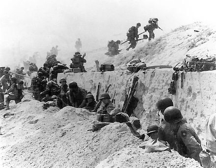 U.S. soldiers of the 8th Infantry, 4th Infantry Division advance over the sea-wall at Utah. Troops move out over the seawall on Utah Beach.jpg