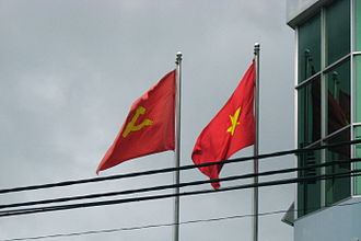 Communist Party of Vietnam - Two flags—the flag of the Communist Party, and the national flag of Vietnam—flying side by side.
