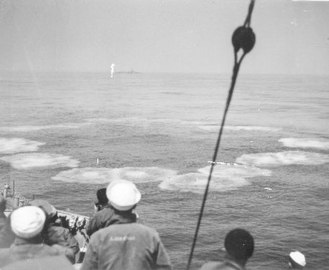 Sailors observe a ring of small circular waves from the impact of Hedgehog bombs into the water