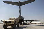 U.S. Air Force Staff Sgt. Ryan Vanterpool, an aerial porter with the 455th Expeditionary Aerial Port Squadron, coordinates the loading of a mine-resistant, ambush-protected vehicle onto an Air Force C-17 131002-F-YL744-019.jpg