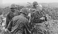 A black and white image of Merritt Edson and three other Marines standing in bushes. Edson is holding some binocculars and is looking out over the battlefield.