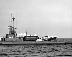A rocket taking off horizontally from the deck of a surfaced World War II-era submarine