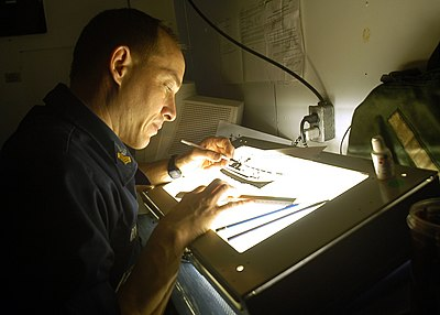 US Navy 030209-N-2972R-079 Illustrator Draftsman designs a training slide with the assistance of a light table.jpg