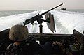US Navy 030328-N-5362A-004 A U.S. Naval Special Warfare Combatant Craft (SWIC) crewman sits beside his .50 caliber machine gun mounted on the back of a Special Operations Craft -Riverine as it transits through Iraq's southern w.jpg