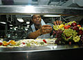 US Navy 040614-N-0995C-002 Culinary Specialist Bryant Scott arranges a fruit sculpture on the forward mess decks aboard the aircraft carrier USS John F. Kennedy (CV 67).jpg