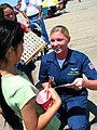 US Navy 060514-N-8374E-002 Aviation Maintenance Administrationman 2nd Class Desiree Phillips, assigned to Maintenance Control on the Blue Angels enlisted team, autographs memorabilia for enthusiastic young fans.jpg