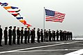 US Navy 071215-N-8237B-003 The American Flag and pennants fly above Sailors and Marines as they form up on the flight deck.jpg