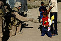 US Navy 071220-M-6159T-015 Lance Cpl. Dylan S. Penrose, assigned to K Co., 3rd Battalion, 3rd Marine Regiment, gives out candy in Karmah, Iraq during a patrol through area neighborhoods to interact with the residents and preven.jpg