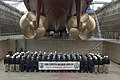 US Navy 080219-N-9520G-001 Sailors assigned to the Arleigh Burke-class guided-missile destroyer USS Curtis Wilbur (DDG 54) pose for a command photo under the ship's screws as the command wraps up a dry dock selective restricted.jpg