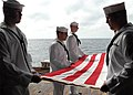 US Navy 081006-N-9134V-055 The burial detail folds the ceremonial flag in honor of a deceased Navy veteran during a burial at sea aboard the amphibious dock landing ship USS Carter Hall (LSD 50).jpg