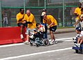 US Navy 081108-N-8816D-396 Chief Equipment Operator Rick Chafee assists his athlete during the wheelchair race during the Special Olympics at the Kadena Air Base in Okinawa.jpg