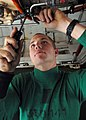 US Navy 081129-N-2456S-055 Aviation Electrician's Mate 3rd Class Lonnie Pope, assigned to VAQ-141, installs a clamp on the starter generator lines of an EA-6B Prowler in the hangar bay aboard the aircraft carrier USS Theodore R.jpg