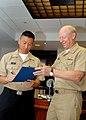 US Navy 081219-N-5476H-010 Navy Counselor 1st Class Matthew Johnson signs his reenlistment papers during a reenlistment ceremony conducted by Adm. Robert F. Willard.jpg