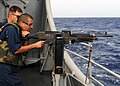 US Navy 090319-N-1082Z-021 Chief Gunner's Mate David C. Brown monitors Ship's Serviceman 3rd Class Romulo Casavilca during an M240B machine gun qualification shoot aboard the guided-missile cruiser USS Vella Gulf (CG 72).jpg