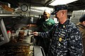 US Navy 100423-N-9818V-144 Master Chief Petty Officer of the Navy (MCPON) Rick West flips burgers with Culinary Specialist Seaman Mykal Martin aboard the Virginia-class attack submarine USS New Mexico (SSN 779).jpg