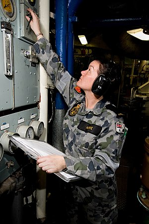 Marine technology - A Royal Australian Navy female marine technician from Moora, Australia taking pressure readings on a diesel generator in an enclosed operating station.