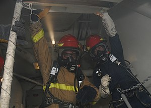 US Navy 111220-N-NB694-113 Sailors hold up a hatch to access a space while fighting a simulated fire during a general quarters drill aboard the Nim.jpg