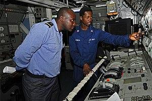 US Navy 120209-N-IZ292-079 Gas Turbine System Technician (Mechanical) 3rd Class Botha Nzinga explains the propulsion control console aboard the gui.jpg