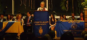 "Picture of speaker making speech, with others on podium, with words ""Phi Theta Kappa"" on banner"
