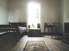 Vue d'une chambre avec un lit, une table et une chaise