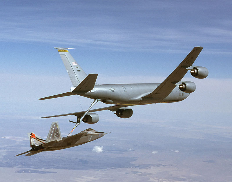 Rear/starboard view of aerial refueling tanker transferring fuel to a jet fighter via a long boom. The two aircraft are slightly banking left.