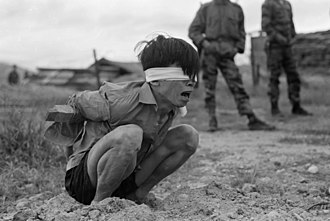 A suspected Viet Cong prisoner captured in 1967 by the U.S. Army awaits interrogation. He has been placed in a stress position by tying a board between his arms. Vietconginterrogation1967.jpg