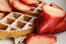 Round waffle topped with strawberries and powdered sugar