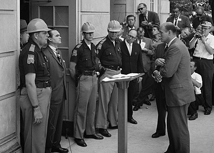 Wallace standing against desegregation while being confronted by Deputy U.S. Attorney General Nicholas Katzenbach at the University of Alabama in 1963 Wallace at University of Alabama edit2.jpg