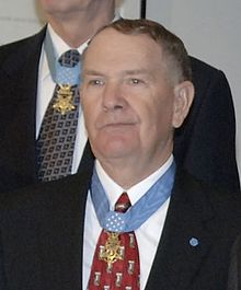 Head and shoulders of an older man with thinning hair wearing a dark suit coat, white shirt, and red tie. A star-shaped medal hangs from a light blue ribbon around his neck and on his lapel is a small round blue pin.