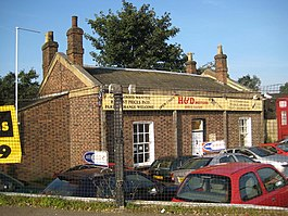 small red brick ticket office used as a car sales office