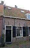 foto van Eenvoudig woonhuis met gepleisterde gevel onder een gezamenlijk, met de nrs 4,6 en 8, dwars, met pannen belegd zadeldak