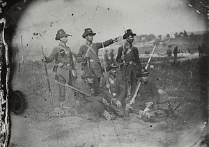 Iron Brigade - Union Army soldiers, from the 2nd Wisconsin Volunteer Infantry Regiment, Company C, of the Iron Brigade, wearing a mix of blue and gray uniforms and the distinctive hardee hats. The state militia uniforms were eventually replaced to avoid being mistaken as Confederate soldiers. From a rare, degraded, tintype photograph, circa 1861.