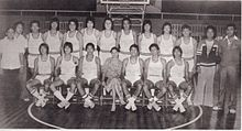A black and white photograph of people standing in two rows in front of a basketball hoop. The back row mostly has men wearing white sleeveless shirts and white shorts while standing, while the front row has men wearing white sleeveless shirts and white shorts seated on chairs except for a woman in the center wearing a dress.