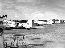 Black and white photograph of five silver aircraft parked in a line