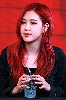 Rosé sits at a table holding a microphone, looking sideways.