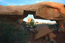 Mano Arch—much thicker than Metate Arch—with several boulders lying under it and a large notch missing from the bottom of the arch. A distant hoodoo appears framed inside the arch's notch.