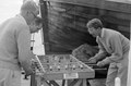 """ASC Leiden - NSAG - van Es 22 - 009 - Three students play table football on the ship's deck. The large lifeboat """"Amsterdam"""", Holland West Africa Line - From Dakar to Genoa - 1962.tif"""
