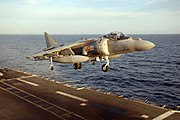 Grey jet aircraft executing a vertical takeoff from aircraft carrier at sea. Under each of the angled-down wings is an external fuel tank.